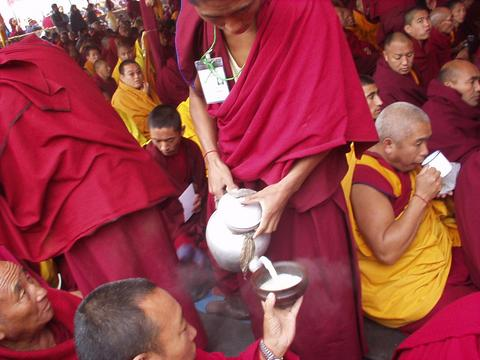 Monk serving milk tea at the Kalachakra Initiation.