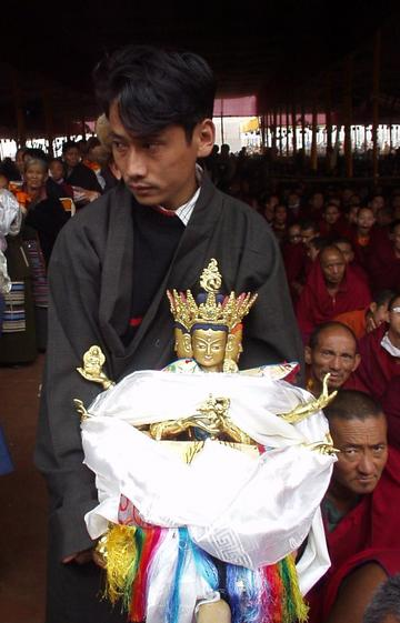 Tibetan man waiting in line with an idol at the 2003 Kalachakra Initiation, Bodhgaya.