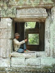 Cambodian man lounging in a window at Ta Prohm, Angkor.