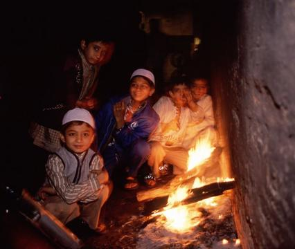 Boys sitting next to a fire in an alley off of a street market in Delhi.