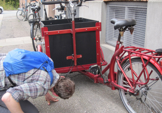 Visiting Copenhagen is like visiting a bicycle zoo: there is an example of every species, including a lot of utility bikes.  Here, Joe studies the steering system of a Christiania bike.