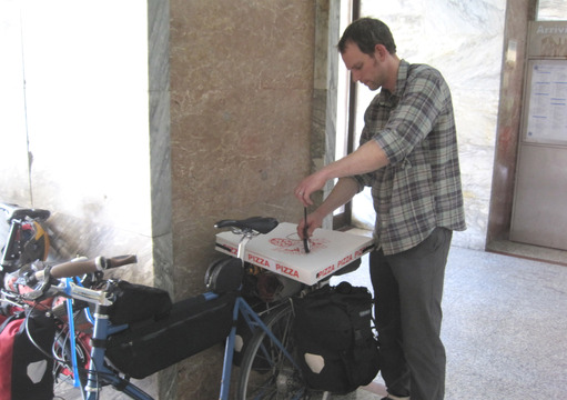 Traveling in Europe creates interesting challenges for carrying food. Here, Joe readies a pizza to be carried on his bike rack in Florence, Italy.