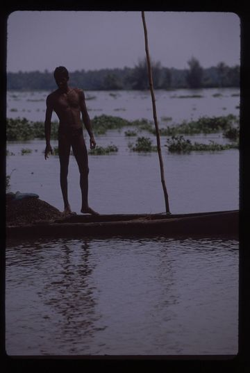 Man standing on his pole-boat at dusk in the backwaters near Fort Cochin, Kerala state.