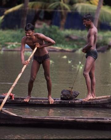 Men poling their boats in the backwaters near Fort Cochin, Kerala state.