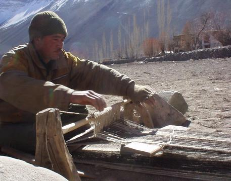 Ladakhi man weaving a woolen mat in the town of Alchi.