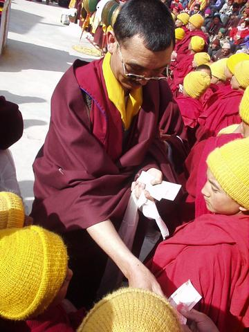 Monk distributing monetary gifts to young monks at the Spituk Festival, 2003.
