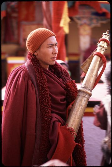Monk carrying a Tibetan great horn, or dungchen, at the Spituk monastery winter festival.