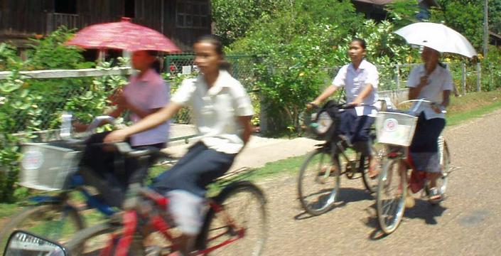 Girls bicycling around the village of Champasak, southern Laos.