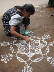 Woman drawing a Kolam outside of her business, Madurai.