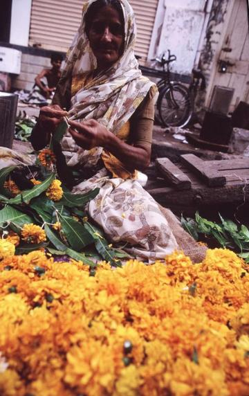 Woman selling strings of marigolds for Diwali.