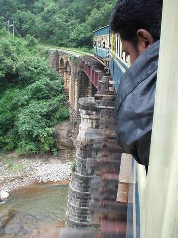 Indian man looking out the winow of the Ooty train.