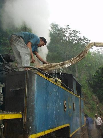 Man filling the Ooty train's locomotive with water.