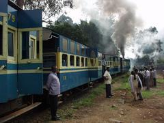 People waiting outside of the Ooty train at a watering stop.