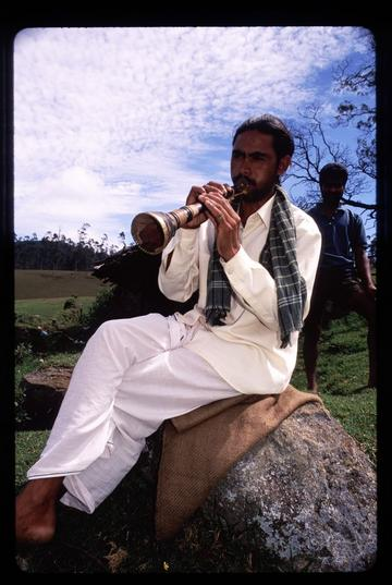 Man playing a flute in the hills near Ooty, Tamil Nadu. These men were herders of water buffalo and played the flute to pass the time in the fields.