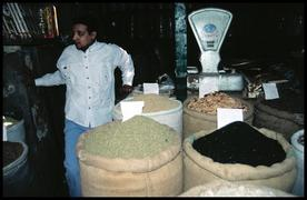 A merchant in his shop with his bags of spices.