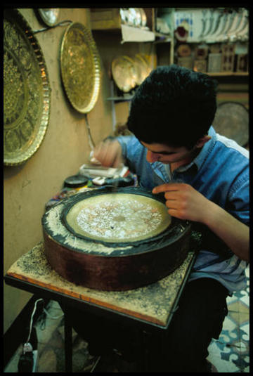 Inlaid metal plates and wooden boxes are the stock souvenirs for Damascus. Here, a boy hammers away for a living in a storefront, doubling as an advertisement for the wares.
